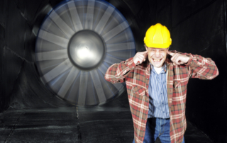 An engineer, covering his ears to protect them from the noise of a wintunnel being tested